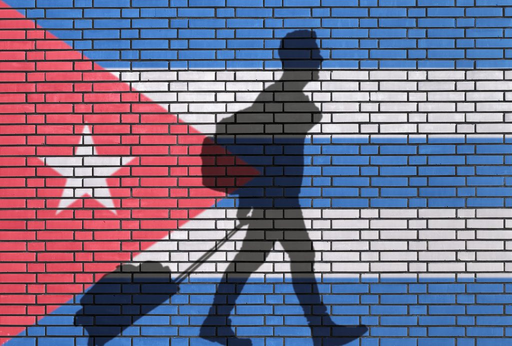 Cuban-Flag-behind-man-with-Suitcase-1024x692